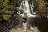 Rear view of mature woman practicing with open arms in front of waterfall Stock Photo - Premium Royalty-Freenull, Code: 649-08180546