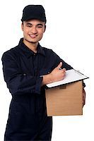 Young cheerful asian courier boy delivering you carton Stock Photo - Royalty-Freenull, Code: 400-08186476