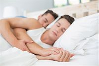 Homosexual couple sleeping on bed Stock Photo - Premium Royalty-Freenull, Code: 6109-08203711