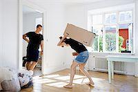 Man watching girlfriend carry heavy box Stock Photo - Premium Royalty-Freenull, Code: 6122-08212083