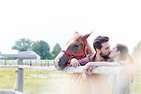 Couple with horse kissing at rural pasture fence Stock Photo - Premium Royalty-Freenull, Code: 6113-08220439