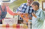 Grandparents and grandson tasting and selling honey at farmer's market stall