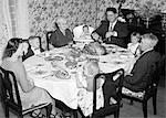 1950s THREE GENERATION FAMILY HAVING THANKSGIVING HOLIDAY MEAL IN DINING ROOM FATHER CARVING TURKEY