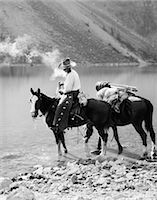 1920s 1930s MAN COWBOY ON HORSE WITH PACK HORSE BY MORAINE LAKE ALBERTA CANADA Stock Photo - Premium Rights-Managednull, Code: 846-08226096