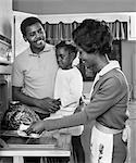 1960s AFRICAN AMERICAN FAMILY IN KITCHEN FATHER AND DAUGHTER WATCHING MOTHER REMOVE ROAST TURKEY FROM OVEN