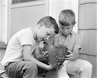 1970s TWO BOYS SERIOUSLY INSPECTING NEW LEATHER BASEBALL MITT SITTING ON PORCH Stock Photo - Premium Rights-Managednull, Code: 846-08226111