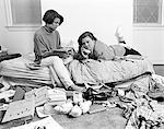 1980s TWO TEENAGE AFRICAN AMERICAN GIRLS IN CLUTTERED BEDROOM ONE TALKING ON THE PHONE ONE READING MAGAZINE