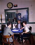 1960s COLLEGE RADIO STATION DJ INTERVIEWING MAN & WOMAN AROUND MICROPHONE AT TABLE ON AIR SIGN CONTROL ROOM BROADCASTING