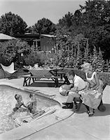 1950s 1960s BACKYARD PATIO POOL PARENTS MOTHER FATHER MAN WOMAN SEATED WATCHING THREE CHILDREN PLAYING IN WATER Stock Photo - Premium Rights-Managednull, Code: 846-08226169