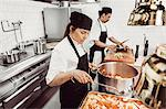 Multi-ethnic chefs preparing food in commercial kitchen