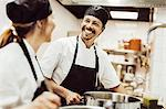 Happy male chef looking at colleague while cooking in kitchen