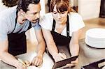 High angle view of chefs using digital tablet while writing recipe at commercial kitchen counter