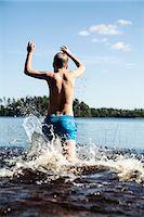 Rear view of boy running in lake Stock Photo - Premium Royalty-Freenull, Code: 698-08226500