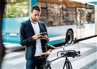 Businessman using mobile phone while standing with bicycle on city street Stock Photo - Premium Royalty-Freenull, Code: 698-08226610
