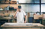 Carpenter working at workbench in workshop