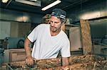 Carpenter holding wooden plank at workshop