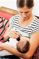 Mid adult woman breastfeeding baby girl at home Stock Photo - Premium Royalty-Freenull, Code: 698-08226743