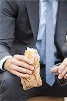 sandwich wrapper - Businessman holding sandwich, cropped Stock Photo - Premium Royalty-Freenull, Code: 632-08227482