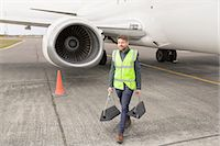 Mid adult man wearing high visability jacket walking past airplane engine carrying chocks Stock Photo - Premium Royalty-Freenull, Code: 649-08232653