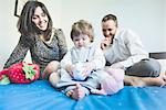 Mid adult couple playing with toddler daughter on bed