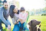 Mid adult couple with toddler daughter and dog in park