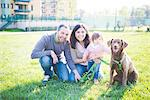 Portrait of mid adult couple with toddler daughter and dog in park
