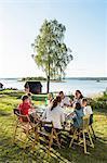 Family having meal at lake