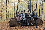 Girls chatting on tree trunk in autumn forest