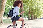 Portrait smiling woman riding bicycle with mp3 player and headphones in park