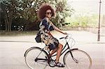 Portrait smiling woman with afro riding bicycle in urban park