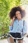 Enthusiastic woman with afro riding bicycle listening to music on headphones