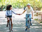 Couple holding hands riding bicycles in urban park
