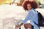 Smiling woman with afro riding bicycle in urban park
