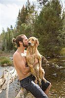 Young man kissing his wet dog at river, Lake Tahoe, Nevada, USA Stock Photo - Premium Royalty-Freenull, Code: 614-08329425