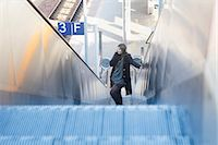 Young woman moving on escalator and talking on phone at railway station, Freiburg im Breisgau, Baden-Württemberg, Germany Stock Photo - Premium Royalty-Freenull, Code: 6121-08361699