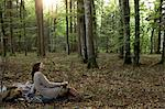 Side view of mature woman sitting in forest on picnic rug holding coffee cup looking away