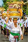 Women carrying religious offerings on their heads at a cremation ceremony for a high priest in Ubud, Bali, Indonesia