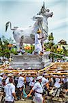 People carrying a raised, white bull character in a parade at a cremation ceremony for a high priest in Ubud, Bali, Indonesia