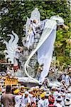 People carrying an elaborate parade float at a cremation ceremony for a high priest in Ubud, Bali, Indonesia
