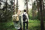 Rear view of couple carrying backpacks while walking through forest