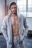 Fit shirtless man with hooded jumper Stock Photo - Premium Royalty-Freenull, Code: 6109-08398072