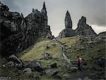 Two people with rucksacks on a narrow path rising to a dramatic landscape of rock pinnacles on the skyline towering above them, under an overcast sky with low cloud.