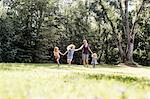 Mid adult woman and three young daughters holding hands and running in park