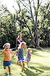 Mid adult woman running and holding hands with three  daughters in park