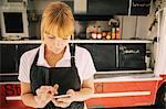 Close-up of female chef using mobile phone against food truck