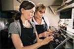 Female chefs using technology in food truck