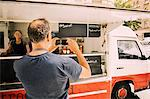 Rear view of owner photographing street food truck in mobile phone
