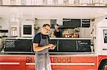 Mature chef using mobile phone against street food truck