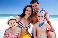 Cute family posing for camera with boy wearing snorkeling equipment on the beach Stock Photo - Premium Royalty-Freenull, Code: 6109-08434792
