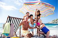 Cute family setting their umbrella on the beach Stock Photo - Premium Royalty-Freenull, Code: 6109-08434840